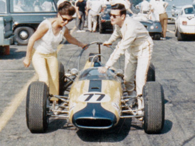 Owner Eva H Kirk and driver Allen Treuhaft push their Brabham BT10 through a race paddock in 1967. Copyright Frederick Amey 2020. Used with permission.