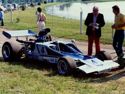 Warren Flickinger's Lola T300 waits in the paddock at Mid-Ohio in 1973. Copyright Terry Capps  2013. Used with permission.