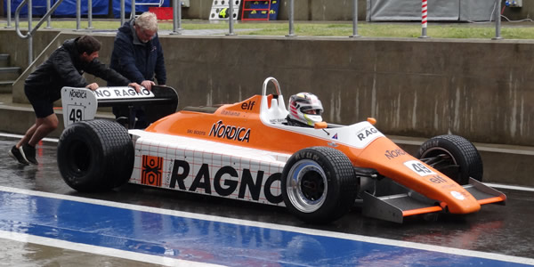 Historic motor racing is pure glamour.  Neil Glover is pushed down the Wing pit road after practice for the 2015 Silverstone Classic in his A5-specification Arrows. Copyright Keith Lewcock  2015. Used with permission.