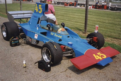 Bill Faircloth's Lola T332 at Mid-Ohio in 1996 or 1997.  Note the holes in the scoop bodywork near the roll hoop and near the h in Faircloth for the roll cage that Thomas used. Copyright Bill Peters 2001. Used with permission.